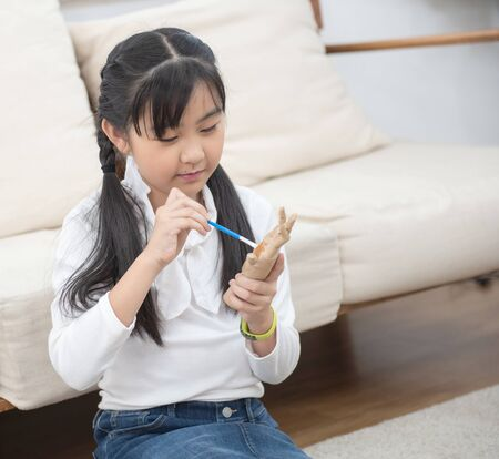 art asian girl student holding paint brush and learning paint on wood doll in living room at home on leisure weekend.