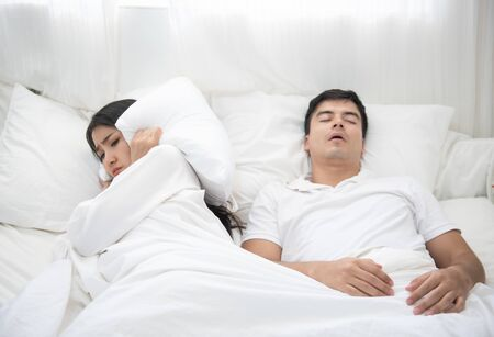 Young interracial couple, Asian woman, Caucasian man sleeping in bed at home. Snoring man. Couple in bed, man snoring and woman can not sleep, covering ears with pillow for snore noise.