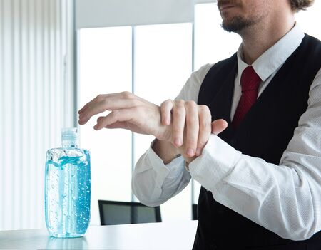 Caucasian business man in office using alcohol gel and rubbing hands back and forth to kill virus. protect from coronavirus or covid-19 virus world pandemic,health care and medicine concept.