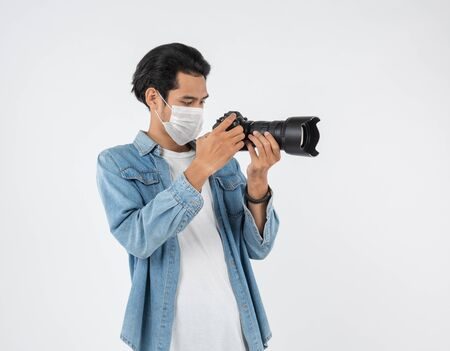 Protection against contagious disease, coronavirus.Asian camera photographer young man wearing hygienic mask prevent infection,airborne illness,Covid-19 shot in studio isolated on white background.