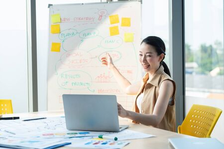 Asian beautiful entrepreneur working and talking video online with laptop and chart board in office or home desk, work at home and social distancing protect coronavirus or covid-19 health care concept Archivio Fotografico