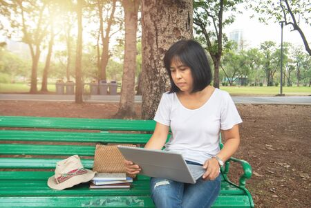 Asian mid adult entrepreneur businesswoman sit in park using laptop for work outside office in casual dress looking notebook with thinking and concentrate in park. Stock Photo