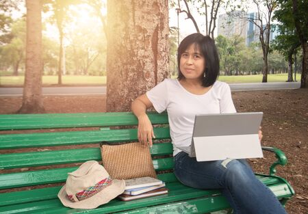 Asian mid adult entrepreneur businesswoman sit in park using laptop for work outside office in casual dress looking notebook with thinking and concentrate in park.