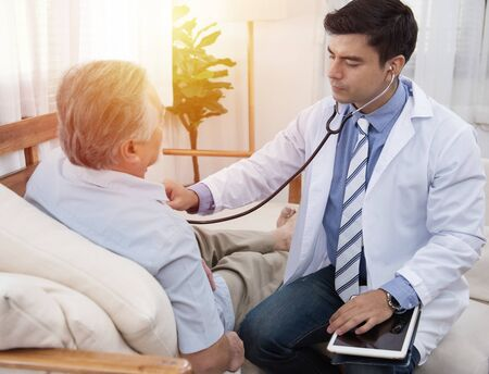 Caucasian doctor sit on chair check asian senior elderly old man heart beat lay down on sofa at home.Medicine and healthcare concept.
