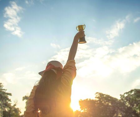Back or rear view of long hair women hands hold gold trophy cup on blue sky with cloud and sunrise background, for symbol of victory and success for business concept. Banque d'images