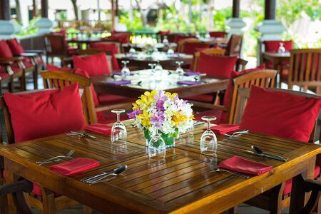 colorful beautiful orchid bouquet decor in glass vase setup on wooden dinner table in India wedding venue reception.