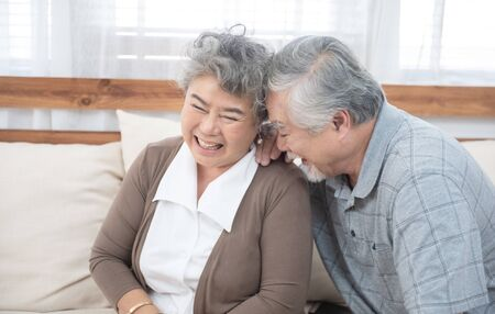 Romantic and happy asian elder senior couple laughing while sitting on sofa at home Stock Photo