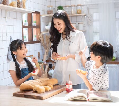 Happy asian family in the kitchen. mother and son and daughter spread strawberry yam on bread, leisure activities at home.