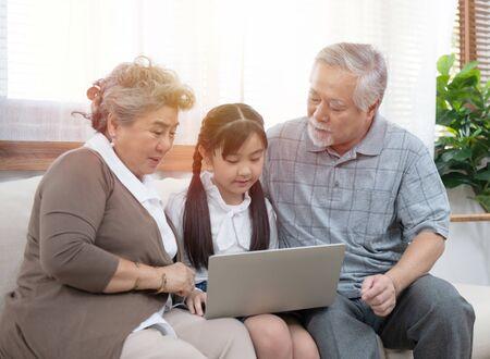 Kleine Enkelin bringt Senioren bei, mit Computer und Technologie und modernem Lebensstil im Internet zu surfen. Standard-Bild