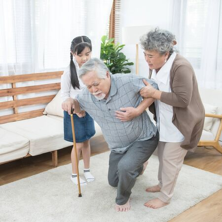 Asian grandfather fall down grandmother and granddaughter help and support carry him to sit on sofa,retirement life concept.