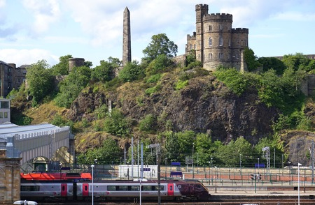 edinburgh background: Waverley Railway Station, Edinburgh, Scotland, with the Governors House and Obelisk on Calton Hill in the background