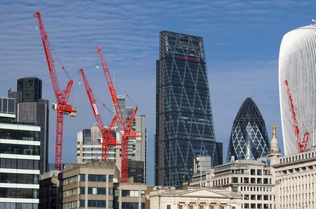 to dominate: LONDON, UK - OCTOBER 11 2015: Red construction cranes dominate the skyline in the City of London. Editorial
