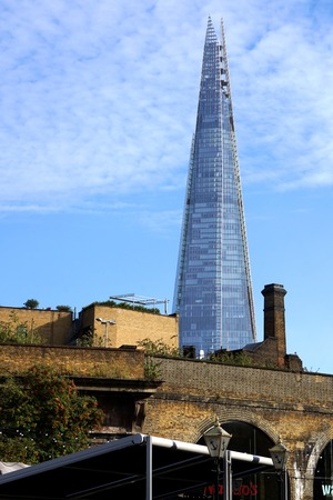 renewing: LONDON, UK - OCTOBER 11 2015: Modern landmark The Shard rises up behind an old brick bridge and buildings near Borough Market in Southwark, London. Editorial