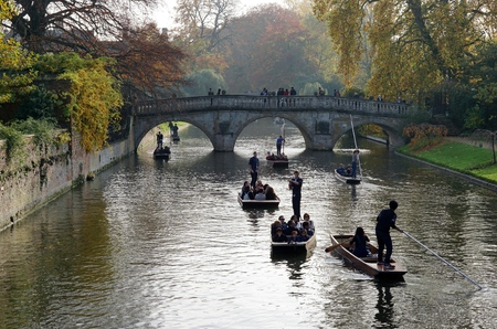 CAMBRIDGE, UK - OCTOBER 31 2015: Tourists punt down the River Cam near the Clare Bridge, Cambridge's oldest bridge, on a sunny autumn afternoon. Editorial