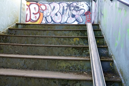 runnel: CAMBRIDGE, UK - APRIL 25 2015: A bicycle stairway runs up the side of a graffitied railway bridge staircase, part of a cycle-friendly network of paths near Cambridge, England. Editorial