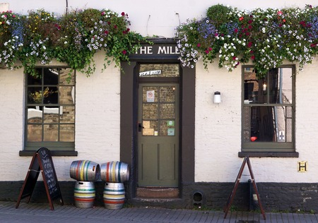 casks: CAMBRIDGE, UK - SEPTEMBER 30 2015: Flower baskets and beer casks decorate the front of The Mill, a traditional city pub in Cambridge, England.