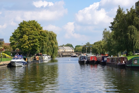 cambridgeshire: ELY, UK - SEPTEMBER 15 2015: Colourful river boats and canal boats line the banks of the River Great Ouse in Ely, Cambridgeshire. Editorial