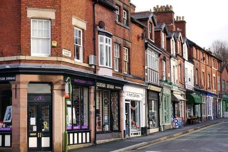 fila: Leek, Reino Unido - 31 de diciembre de 2015: Una fila de tiendas pequeñas e independientes ocupa la planta baja de casas adosadas de ladrillo rojo históricos a lo largo de la calle Fuente en Leek, una ciudad histórica en los páramos de Staffordshire, Inglaterra.