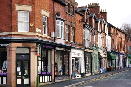 the row: LEEK, UK - DECEMBER 31 2015: A row of small, independent shops occupies the ground floor of historic red brick terraced houses along Fountain Street in Leek, a historic market town in the Staffordshire Moorlands, England.