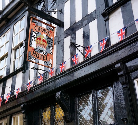 daub: NANTWICH, UK - DECEMBER 29 2015: A string of British flags decorates a historic wattle and daub black and white hotel in the centre of the ancient salt town of Nantwich, Cheshire.