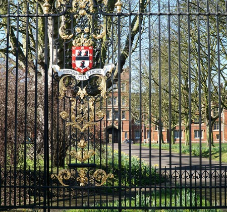 motto: CAMBRIDGE, UK - FEBRUARY 16 2016: A coat of arms displaying Jesus Colleges symbol, the black cockerel, and its Latin motto, Prosperum iter facias May your journey be successful decorates the railings at the Victoria Avenue entrance to the college, in Cam Editorial