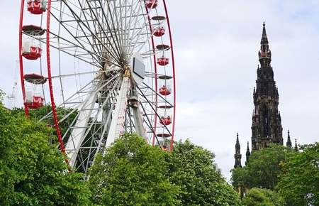 treetops: EDINBURGH, UK - JULY 18 2015: A red and white Ferris Wheel and the Gothic Walter Scott Monument rise above the treetops in Princes Street Gardens, Edinburgh, Scotland. Editorial