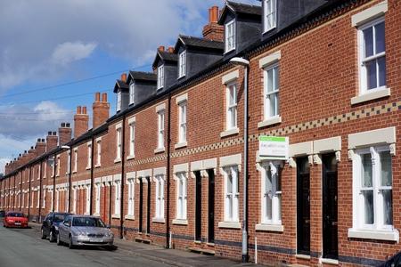 STOKE-ON-TRENT, Verenigd Koninkrijk - 29 maart 2016: Een te koop bord hangt voor een rijtjeshuis, een deel van een straat van de onlangs gerestaureerde woningen in Burslem, Stoke-on-Trent.