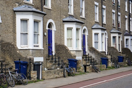 wheelie: CAMBRIDGE, UK - AUGUST 8 2015: Bicycles and blue recycling wheelie bins sit outside the front doors of a row of terraced houses in a residential street with a bike lane in Cambridge, England.