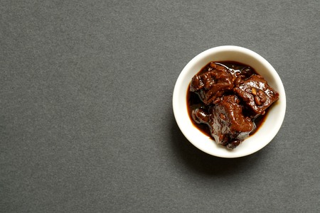 Chinese red fermented tofu, a preserved condiment made from bean curd (sometimes called bean curd cheese), in a small white dipping bowl on grey background.