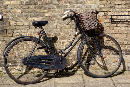 Old style black ladies' bike with wicker basket leaning against a yellow brick wall in Ely, Cambridgeshire.