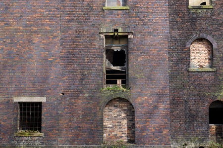 boarded: Side view of an abandoned red brick warehouse or factory building with boarded up and broken windows in Stoke-on-Trent, England