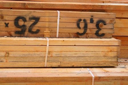 Part of a stack of orange treated cut lumber beams, marked with measurements