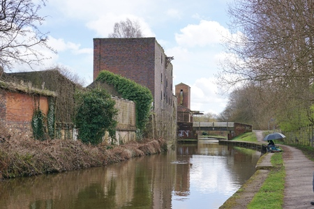 urban decline: STOKE-ON-TRENT, UK - MARCH 29 2016: A lone man fishes from a public footpath, alongside a canal running through a derelict industrial area of Stoke-on-Trent, England.