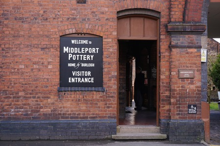 STOKE-ON-TRENT, UK - MARCH 29 2016: A man stands in side the dimly lit visitors office at the entrance of the Middleport Pottery factory museum.