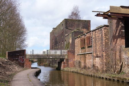 STOKE-ON-TRENT, UK - MARCH 29 2016: A pedestrian bridge crosses a canal bordered by run-down industrial buildings in Middleport, Stoke-on-Trent.