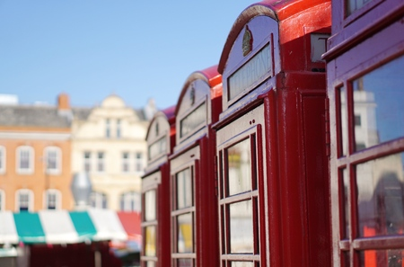 CAMBRIDGE, UK - AUGUST 22 2015: Four red British telephone boxes sit in a row near the city centre market square in Cambridge, England.