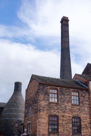 STOKE-ON-TRENT, UK - MARCH 29 2016: Clouds swirl behind the chimney and brick bottle kiln of the restored Middleport Pottery factory works in Burleigh, Stoke-on-Trent, as seen from public footpath. Editorial