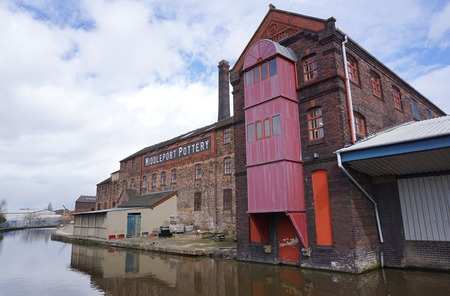 STOKE-ON-TRENT, UK - MARCH 29 2016: A historic warehouse building sits alongside a canal in an industrial area of the Potteries, England.