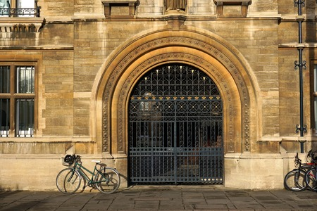 Parked bikes leaning against historic stone building of Gonville And Caius College, Cambridge, by ornamental iron gate.