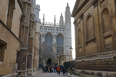 british ethnicity: CAMBRIDGE, UK - DECEMBER 20 2015: A group of Asian tourists exits Kings College Chapel during a sightseeing tour of Cambridge, England.