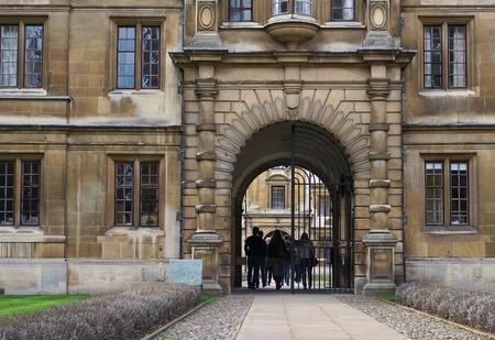 campus tour: CAMBRIDGE, UK - DECEMBER 20 2015: Visitors walk through the main gate of Clare College, Cambridge, England. Editorial