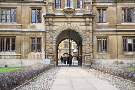 CAMBRIDGE, UK - DECEMBER 20 2015: Visitors walk through the main gate of Clare College, Cambridge, England. Editorial