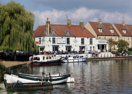 cambridgeshire: ELY, UK - SEPTEMBER 20 2015: People walk alongside the River Great Ouse and eat on the patio of a riverside pub in the small tourist town of Ely, Cambridgeshire.