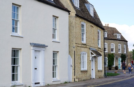 residential street: ELY, UK - SEPTEMBER 20 2015: A couple walk their dog along a residential street of detached period houses in the centre of the small, historic cathedral city of Ely, in Cambridgeshire, England.