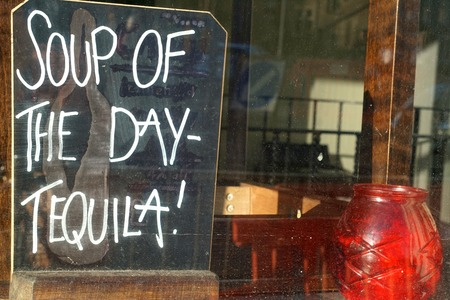 advertises: CAMBRIDGE, UK - SEPTEMBER 20 2015: A sign in a restaurant window advertises a liquid lunch.