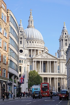 LONDON, UK - OCTOBER 11 2015: People and traffic travel along busy Ludgate Hill in central London, against the backdrop of St Paul's Cathedral.