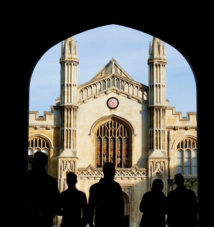 CAMBRIDGE, UK - OCTOBER 31 2015: Silhouetted visitors to Corpus Christi College, University of Cambridge, look through the entrance way arch at the chapel in New Court.