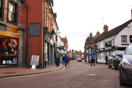 NANTWICH, UK - DECEMBER 29 2015: Shoppers travel along a street of small, independent shops, pubs and restaurants in the town center of historic Nantwich, England.