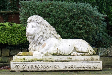 LEEK, UK - DECEMBER 31 2015: A decaying statue of a recumbent lion in Leek, England displays the crest of the Staffordshire Moorlands.