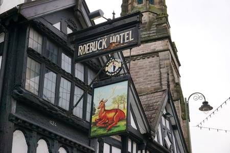 LEEK, UK - DECEMBER 31 2015: A brightly-painted sign for the Roebuck Hotel hangs from a historic wattle and daub building along the high street in Leek, a market town in the Staffordshire Moorlands, England, on a typically grim winter's day.